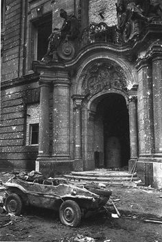 "Berlin May 1945: The majestic entrance to a building in the German capital bears all the scars of the bitter fighting. Parked and ruined in front of the building is a Volkswagen Schwimmwagen literally a ""VW Swim Wagon."" Otherwise known as Type 166 this VW remains the most numerous mass-produced amphibious car in history. Only 163 are known by the Schwimmwagen Registry to remain today and only 13 have survived without restoration work."