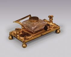 A small early 19th Century Bronze and Ormolu Inkstand, with single glass inkwell, flanked by quill holders having carrying handle and floral decoration to the corners, supported on bun feet. Circa; 1830 Ref: 4399