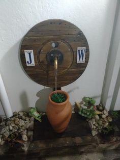 Fonte com madeira de carretel de fios e pote de barro