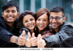 Happy optimistic group of young Asian friends standing with their heads close together laughing and giving a thumbs up gesture - stock photo