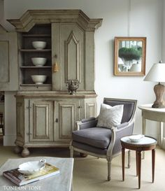 A room setting featuring a 1750s Swedish Baroque cupboard, pair (only one shown) of French painted bergeres with new blue-gray linen upholstery, French mirror with ripple frame and Swedish painted tables.