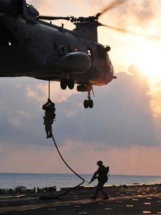 U.S. Marines assigned to the 13th Marine Expeditionary Unit drop from a CH-46 Sea Knight helicopter assigned to Marine Medium Squadron 163 to the flight deck of the amphibious assault ship USS Boxer (LHD 4) while conducting a fast-rope exercise in the Indian Ocean on March 24, 2011. The Boxer is the flagship of the Boxer Amphibious Ready Group, which is underway with the 13th Marine Expeditionary Unit on a western Pacific Ocean deployment.  DoD photo by Petty Officer 3rd Class Trevo