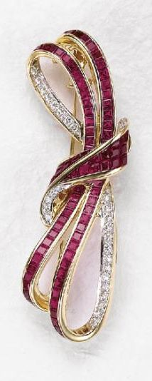 A Diamond and Ruby Brooch  Designed a calibré-cut ruby and circular-cut diamond bow, mounted in 18K yellow gold, length 2 1/4 inches.