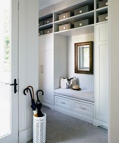 Built-in storage for foyer or mudroom - bench seating with drawers underneath, closets and open storage above.
