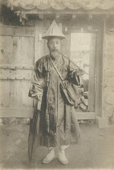 A Korean postman with his umbrella, pipe and mailbag, circa 1900