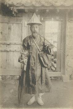 A Korean postman with his umbrella, pipe and mailbag, circa 1900