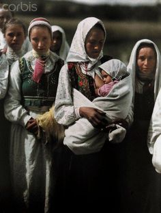 c. October 7, 1930, Bednarka, Poland:   A woman nurses her child while other women stand around her. Photographer: Hans Hildenbrand  National Geographic Society/Corbis