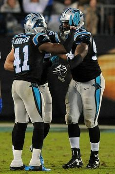 Carolina Panthers defensive end Kony Ealy, right, is congratulated by teammates safety Roman Harper and linebacker Luke Kuechly after he knocked the ball out of Indianapolis Colts quarterback Andrew Luck's, right, hand during first quarter action at Bank of America Stadium in Charlotte, NC on Monday, November 2, 2015. The Panthers defeated the Colts 29-26.