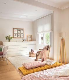 Dormitorio con cómoda y banco a modo de pie de cama con cojines y plaids en rosa…