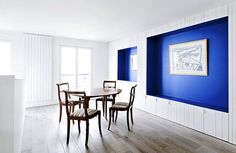 """""""Open kitchen has wall made by the Cabinet and framing international Klein Blue niche for owners of works of art."""""""