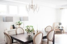 Chic dining room features a French candle chandelier illuminating a dark brown dining table lined with French round back dining chairs, Restoration Hardware Vintage French Round Fabric Side Chairs.