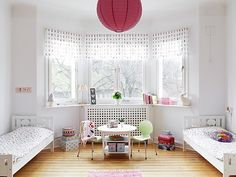 White children's bedroom with patterned bedding, pink spotted accents on the curtains, a small table with two green chairs and a large round pink lantern on the ceiling