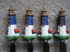 Lighthouse spreader set of 4, (identical). Each spreader is a lighthouse that is brown on top, blue in middle and white on bottom sitting on green grass. Details include three brown windows and two red awning-type projections on each side.