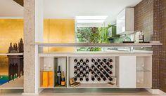 Diseñada en escuadra, la cocina optimiza el área de almacenamiento: de cara al comedor los gabinetes se convierten en bar. Escondida tras los paneles dorados se oculta la nevera