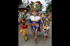 A penitent walks with her children as they take part in a procession for the Moriones Festival during Holy Week in Mogpog town on Marinduque island, central Philippines. During the annual festival, masked and costumed penitents called 'Moriones' dress in attire that is the local interpretation of what Roman soldiers wore during biblical times. Holy Week is celebrated in many Christian traditions during the week before Easter.