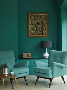 Pair of retro aqua armchairs with tapered legs & aqua painted wall