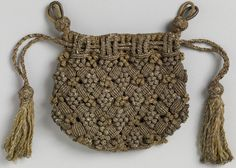 Unlined drawstring bag with two different macrame knots used to produce a diagonal grid-like pattern with diamond-shaped clusters of of tiny balls, in gold and silver metallic yarns.