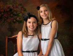 Children's Photography: These two sisters look wonderful in their matching white dresses. Their matching bows and bright smiles will light up the room where this portrait is hung.
