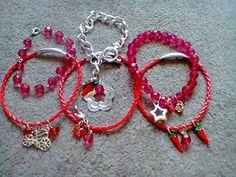 Conjunto de 6 pulseiras, sendo 3 de couro trançado vermelho, 2 em acrílico vermelho e 1 em corrente prata. Pingentes de estrela, flor, sapatinho, bicicleta, laço, pimentinha, cristais, bolinhas acrílicas. R$ 20,00