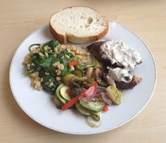 Pork tenderloin with creamy garlic sauce, roasted vegetables, and spinach bulgar salad