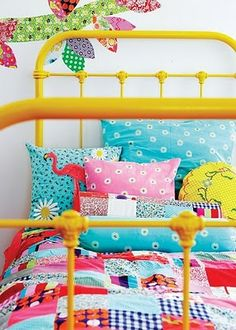 Vintage bed frame painted yellow, colorful bedding.. perfect for little girls.
