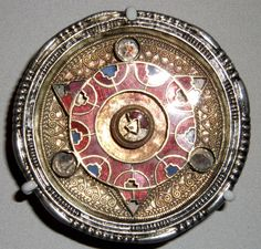 Anglo-Saxon brooch found in Kent, England, dates to about 600-700. The ornate and colourful decoration on this brooch consists of cloisons (cells) inlaid with garnets and blue glass paste. The front is further enriched with filigree wires. The garnets themselves were possibly obtained by sea trade from India.