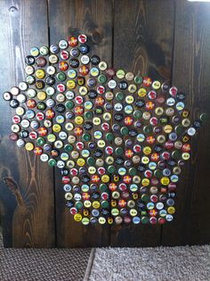 Wisconsin Bottle Cap Art.   Background is made out of wood and stained. Projected outline onto paper and then traced with chalk onto wood. Hot glued the bottle caps, only used Wisconsin caps since I did it in the shape of Wisconsin. :) #wisconsin #bottlecaps #art