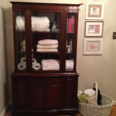 Repurposed china cabinet for towels, blankets and knick-knacks. Wicker Basket to the right to hold more towels for guests.