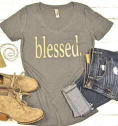 Blessed. That one word says so much! We are obsessed with our NEW slub, heathered dark gray comfy cotton blend tee with our NEW GLAZE in gold!!! This is NOT FOIL! It is a soft, translucent glaze that whispers your message, rather than shouting it! See the model photo above to see how it plays in the light beautifully!! It is only fully visible when light hits it, otherwise it is barely there!!!!  This is a FITTED SHIRT. Please be sure to use the SIZING CHART below! If you are between sizes…