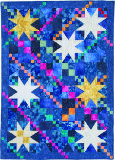 """WHITEHORSE SKY by Friendship Designs: Sue used a wide array of blue fabrics for the background, including tonal prints, mottles, textures and hand- paints. Note you will need additional yardage of the medium blue texture used for the border and binding if you wish to also use some in the back- ground piecing as Sue did. Quilt finishes 35"""" x 49"""". Pattern in the March/April 2017 issue of McCall's Quilting magazine."""