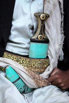 A sheathed Janbiya, Sana'a, Yemen.  Janbiya is the Arabic term for dagger, but it is generally used to describe a specific type of dagger with a short curved blade that is worn on a belt. Although the term janbiya is also used in other Arab countries, it is mostly associated with people of Yemen. Men typically above the age of 14 wear it as an accessory to their clothing. Photograph by Retlaw Snellac, via Flickr.