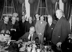 . U.S. President Franklin D. Roosevelt signs the declaration of war following the Japanese bombing of Pearl Harbor, Dec. 7, at the White House in Washington, D.C., Dec. 8, 1941 at 3:08 p.m. EST.  Watching from left to right are, Rep. Sol Bloom, D-N.Y.; Rep. Luther Johnson, D-Texas; Rep. Charles A. Eaton, R-N.J.; Rep. Joseph Martin, R-Mass.; Vice President Henry A. Wallace; House Speaker Sam Rayburn, D-Texas; Rep. John McCormack, D-Mass.; Sen. Charles L. McNary, R-Ore.; Sen. Alben W. Barkley…