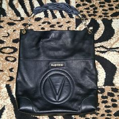 AUTHENTIC VALENTINO CAVINA BAG AUTHENTIC BLACK Valentino Bag by Mario Valentino  Made in Italy!  Original dust bag included with authentic card  MINT CONDITION! No scuffs, scratches, stains or rips/tears Premium leather construction. Magnetic snap closure. Single chain and woven leather carry handle. Signature logo and name plate on front.Flat base. Fully lined interior features back wall zip pocket.  Measurements:  Bottom Width: 14 in Depth: 3 1/2 in Height: 18 in Strap Length: 21 in Strap…