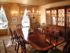 """This charming dining room from HGTV's """"Curb Appeal"""" features rich wood furnishings, heavy window treatments and a brass chandelier."""