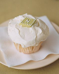 An edible monogram tops a vanilla cupcake, served instead of a slice of wedding cake