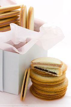 Milan Cookies - Thin, crispy lemon or coconut flavored cookies with either white chocolate raspberry ganache or dark chocolate coconut ganache.