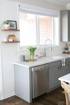 Some cosmetic updates completely transformed this small city kitchen into a bright white oasis! Come check out this white and gray kitchen with brass hardware and wood accessories. So much style in such a small space.