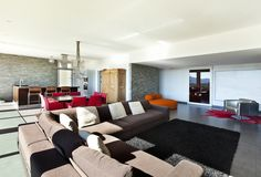 Living room featuring ultra modern look. Contrast is a major theme, with white walls, black shag rug, brown sectional with white pillows, and natural wood bar, table, and cabinet in background. Red features prominently on dining chairs and corner rug.