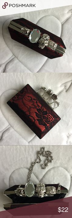 Brass Knuckle Clutch Red & black clutch with brass silver knuckles, with a 24in silver shoulder strap that is attached and can be used or not. Brass knuckles are accented with skull and jewels. Bags Clutches & Wristlets