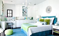 Manny Rodriguez - Chic, modern blue & green girl's bedroom design with silver sunburst mirror, upholstered blue silk headboard with nailhead trim, turquoise blue lamp, blue bed skirt, green pillows, green throw blanket, white nightstands, green leather pouf, blue rug, ghost chair and built-ins desk cabinets shelves. white, blue green girl's bedroom colors.