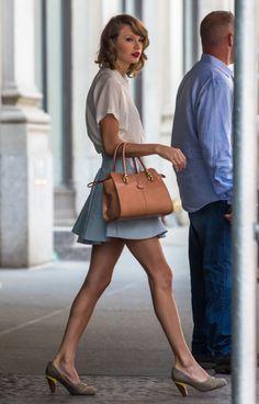 Taylor Swift en jupe skater bleu ciel, chemise masculine, escarpins en daim et sac à main camel