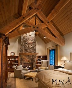 Exposed heavy timber scissor trusses and purlins in bedroom with gable roof. Wood ceiling. Fireplace centered in gable-end wall