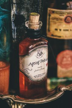 red food coloring in vintage bottle with a clock embellishment on the cork. DYI Harry Potter Potions for Halloween: Ageing Potion - Scrapbook.com