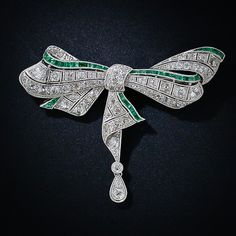 Glistening diamond and emerald ribbons comprise this enchantingly beautiful bow brooch, superbly handcrafted in platinum, circa 1925. Reminiscent of the classic dragonfly motif jewels of the previous Art Nouveau design period, this Art Deco masterpiece blends graceful, flowing curves and artful geometry to create this sublime and sparkling treasure. The bottom ribbon is articulated and the tear drop pendant dances freely.