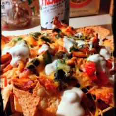 Kickin' Buffalo Chicken Nachos -- These hearty, dude-pleasing nachos are bursting with flavor. The combination of the crunchy tortilla chips with the spicy buffalo chicken and the cool blue cheese dressing make the perfect accompaniment to a frosty cold beverage (or two!)