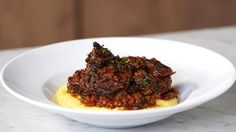 melt in your mouth ossobuco served on a bed of polenta. Ingredients: Oil, 2 ossobucos, Salt, to taste, Black pepper, to taste, 1 carrot, chopped , 1 onion, chopped, 3 cloves garlic, minced, 1 stalk celery, chopped, 1 bay leaf, 4 tablespoons tomato extract, 1 cup dry red wine, 4 cups beef broth, Thyme, to taste, 2 1/2 cups vegetable broth, 3/4 cup instant polenta , 2 tablespoons butter, Grated Parmesan