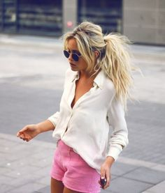 Crazy pulled back hair, white blouse, colored shorts