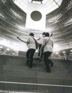 The Beatles step onstage in Tokyo, Japan. 1966.
