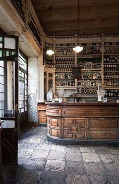 beautiful old cafè. wooden furniture, stone flooring  and shelves full of bottles. everything is antique here. antico bar e caffetteria d'epoca, con mobilia originale, scaffalature d'antiquariato piene di bottiglie e pavimento in pietra #bar #antiques #vintage   Concrete Living #restaurantdesign