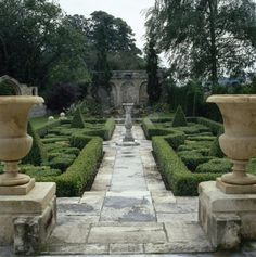 I wonder how beautiful this #topiary garden would be once the hedge growt...love the stone #gardenpath and the urnas